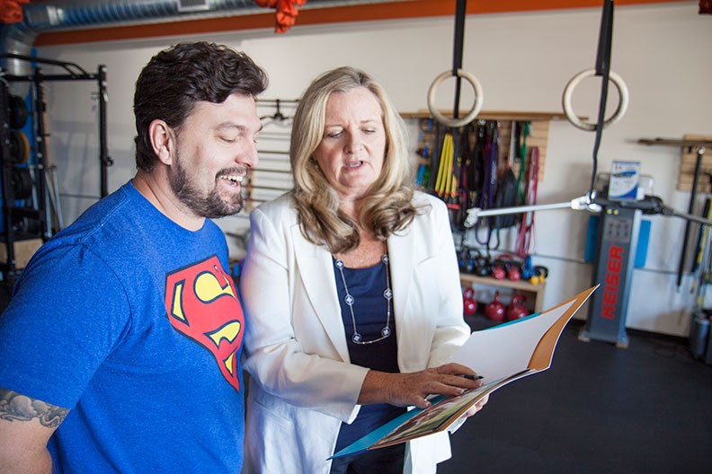 Carol talking insurance with West Seattle business owner